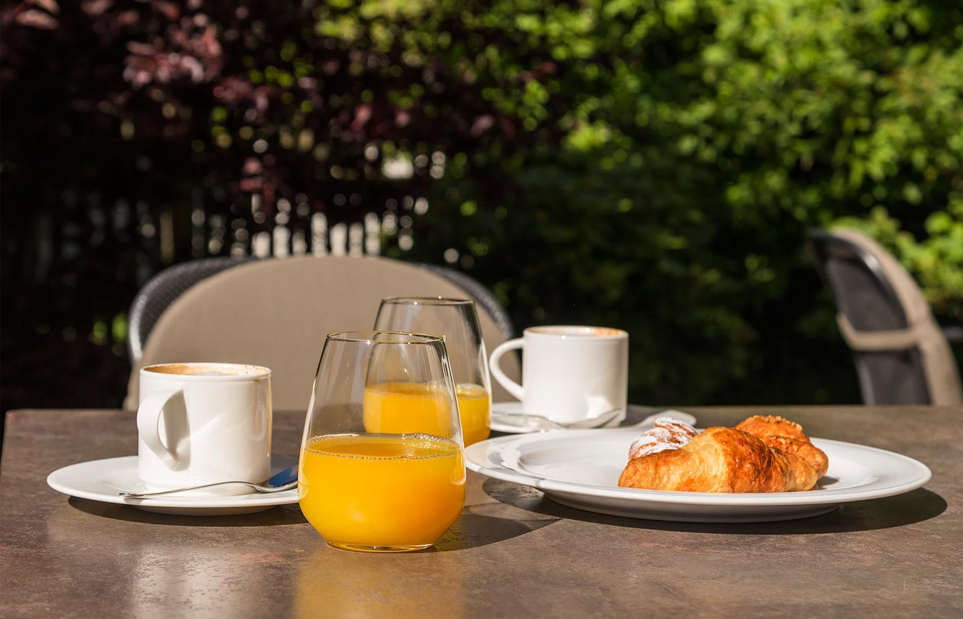 Cappuccino, orange juice and a brioche on a table outdoors