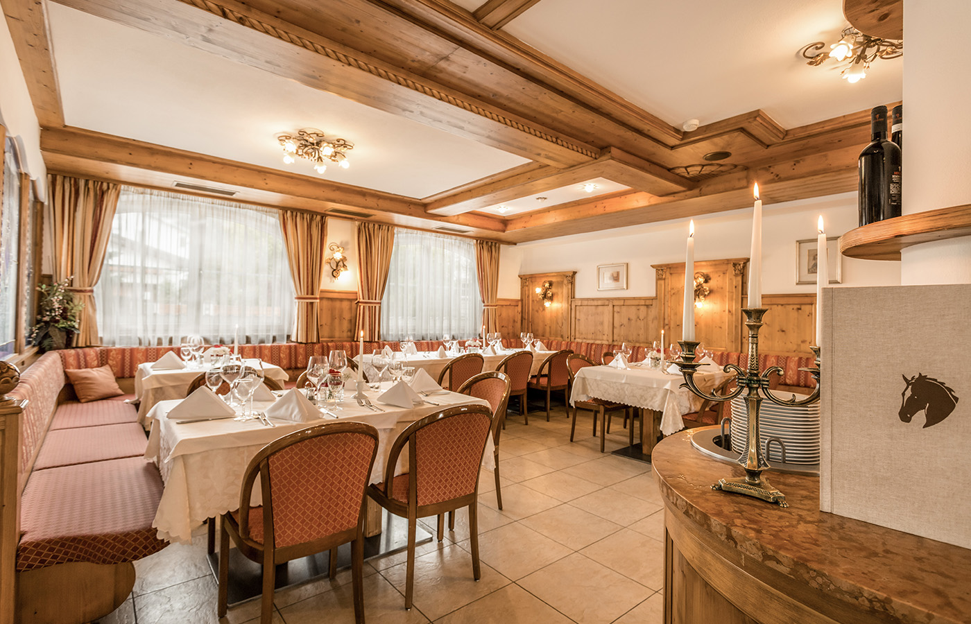 View of wood-panelled restaurant in Vipiteno with lampshades on the wall