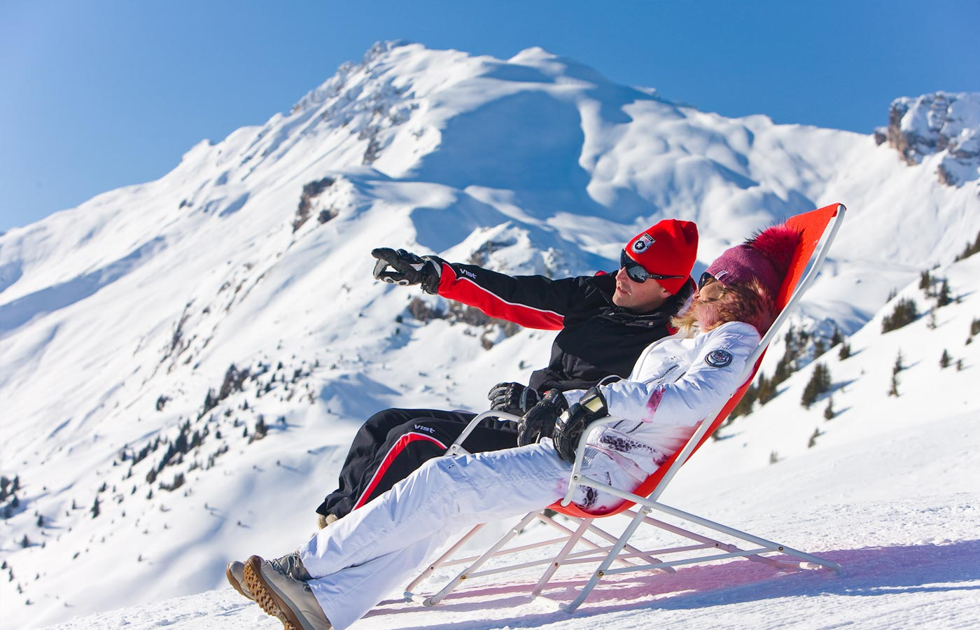 Couple sunbathing on loungers in the snow on the mountains