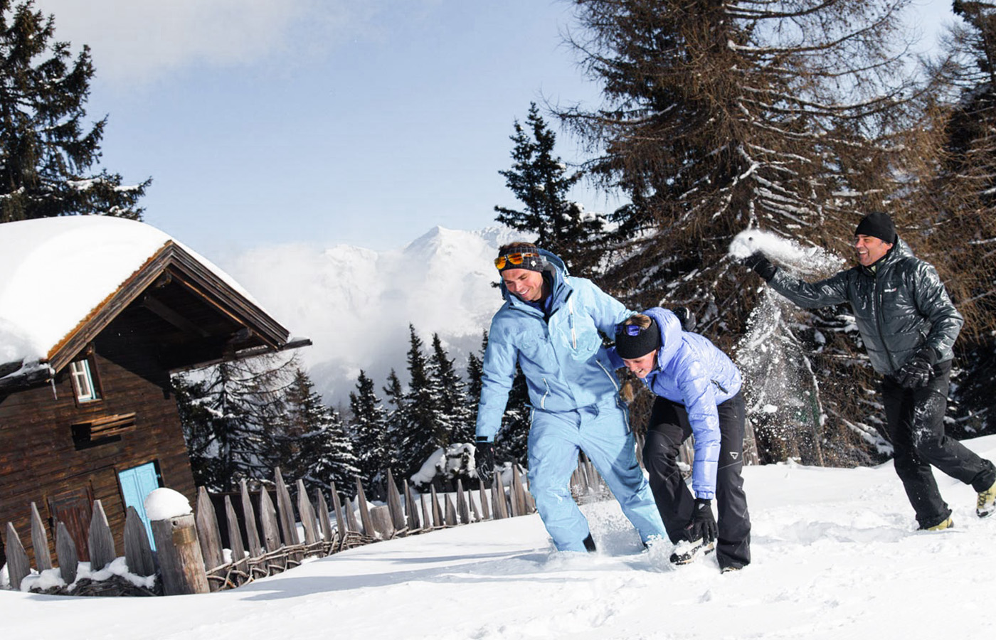 Three people having fun in the snow next to a mountain hut