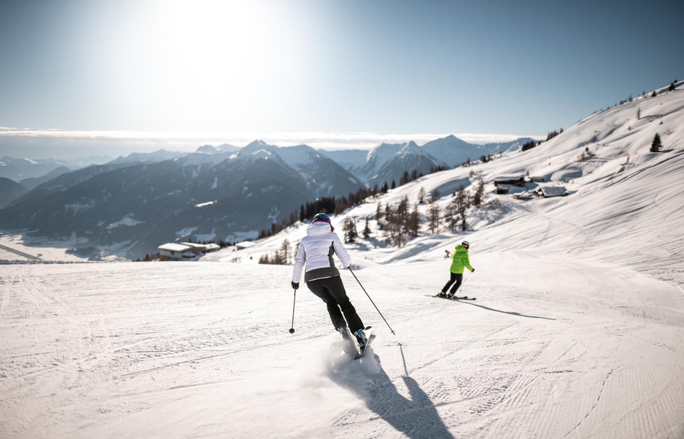 Laughing couple on sun loungers on snowy mountains