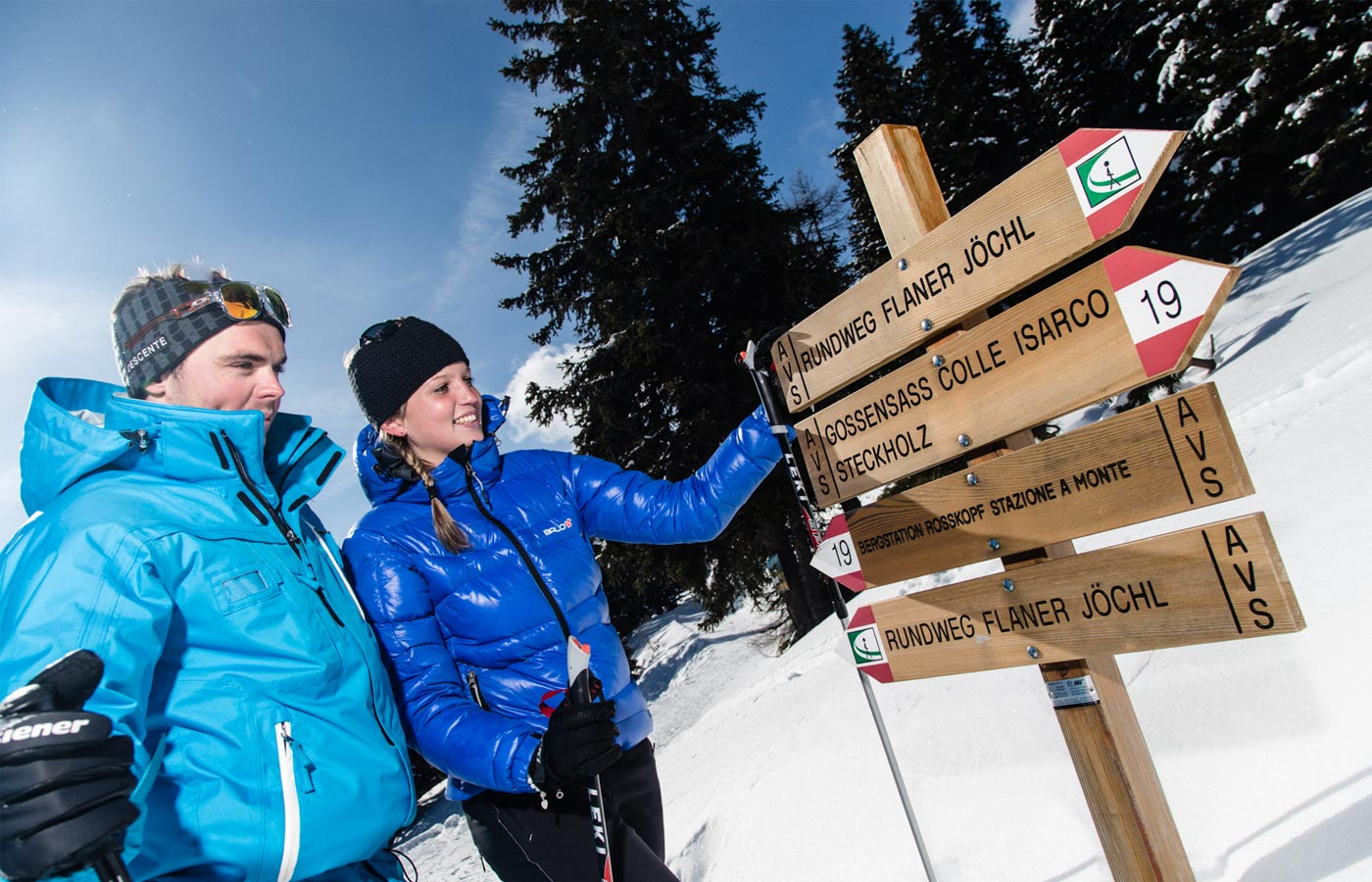 Skier couple pointing at a signpost on a sunny winter's day in the Rosskopf ski area